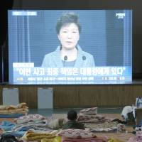 A relative of one of the ferry victims watches a televised address Monday by South Korean President Park Geun-hye at a gymnasium in the port town of Jindo.   AP
