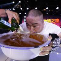 A singer drinks from a huge bowl of beer after performing at a Beijing club on Thursday. | REUTERS