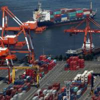Container cranes work at a shipping terminal in Osaka Bay on May 2. | BLOOMBERG