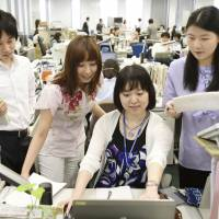 Employees work in casual attire at the Environment Ministry in Tokyo on Thursday. | KYODO
