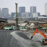 A construction site in the Tokyo Bay area bustles with heavy machinery earlier this month. | BLOOMBERG