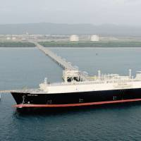 A ship designed to carry liquefied natural gas is berthed at an LNG loading facility in Papua New Guinea.   EXXON MOBIL CORP./KYODO