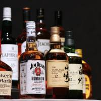 Bottles of Jim Beam bourbon and Yamazaki and Hakushu whisky are displayed at a news conference in Tokyo on Thursday. | BLOOMBERG