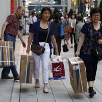 Chinese tourists carry boxes of Panasonic Corp.'s washlet toilet seats along Ginza shopping district in Tokyo last Friday.   REUTERS