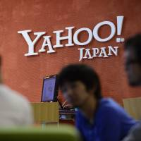 Yahoo Japan Corp. employees speak to a customer in front of the company's headquarters in Tokyo last year. | BLOOMBERG