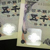 The next version of the ¥5,000 bill (right) is displayed with the current version in Tokyo on Thursday. The bigger and square-shaped hologram sticker with a different texture is aimed at making the bill easier to recognize by visually impaired people, who are becoming a growing segment of Japan's rapidly graying population. The government will start issuing the new banknote Monday. | BLOOMBERG