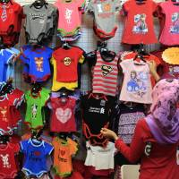 A woman shops for baby clothes in Shah Alam, outside Kuala Lumpur, on Friday. | AP