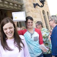 Kristin Seaton holds up her marriage license on Saturday as she leaves the Carroll County Courthouse in Eureka Springs, Arkansas, with her partner, Jennifer Rambo. | AP