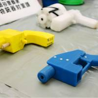 Kanagawa police on Thursday display two guns (yellow and blue) created with a 3-D printer that can fire real bullets.  | KYODO