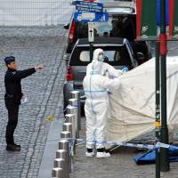 Police personnel work the site of a shooting in central Brussels on Saturday where three people were killed in a shooting at the Jewish Museum. Belgium's interior minister said anti-Semitic motives could be behind the attack. | REUTERS