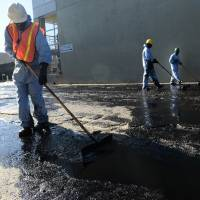 Workers clean up after an oil pipeline ruptured spilling around 10,000 gallons of crude oil into an industrial neighborhood of Los Angeles on Thursday. The oil spread over a half-mile area in Atwater Village, northwest of the city center. | AFP-JIJI