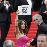 As she arrived for the screening of a film about late fashion designer Yves Saint-Laurent at the Cannes International Film Festival on Saturday, actress Salma Hayek holds up a sign reading 'Bring back our girls.' She was taking part in a campaign calling for the release of nearly 300 abducted Nigerian schoolgirls being held by Nigerian Islamic extremist group Boko Haram. | AP