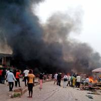Smoke rises following a bomb blast at a bus terminal in Jos, in central Nigeria, on Tuesday. | AP