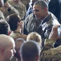 President Barack Obama greets U.S. troops during a surprise visit to Bagram Air Base, near Kabul, on Sunday. He did not visit Afghanistan's departing president, Hamid Karzai, with whom the U.S. has had a rocky relationship. | AFP-JIJI