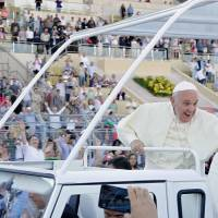 Pope Francis waves to the faithful as he leaves Amman International Stadium on Saturday after holding Mass there. Francis arrived in the West Bank city of Bethlehem on Sunday, the second day of his Mideast pilgrimage. | REUTERS