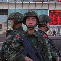 Armed police officers stand guard at the South Railway Station in Urumqi where three people were killed and 79 wounded in a bomb and knife attack, in this image grab from CCTV video shot Wednesday. | REUTERS