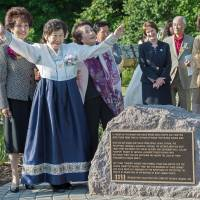 Kang Il-chul, an 85-year-old former 'comfort woman,' raises her hands during ceremonies for the opening of the Comfort Women Memorial Peace Garden in Fairfax, Virginia, on Friday. | AFP-JIJI