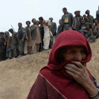 Landslide-affected Afghan villagers line up for relief supplies at the scene of the disaster in Argo district of Badakhshan on Sunday. | AFP-JIJI