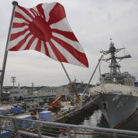 A Rising Sun maritime ensign flutters on the Maritime Self-Defense Force tank landing ship Kunisaki, with a U.S. guided missile destroyer nearby, in Yokosuka, Kanagawa Prefecture, on Tuesday. | AP