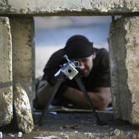 A pro-Russian rebel aims his anti-tank rifle at a front line position from a hiding place between blocks of concrete near the eastern Ukrainian village of Semenivka. | REUTERS