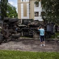 A man stands in front of a truck used by pro-Russian militants after it was bombed by Kiev government forces during overnight during clashes in the eastern Ukrainian city of Donetsk on Tuesday. | AFP-JIJI