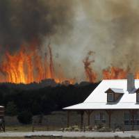 A wildfire threatens a house near Possum Kingdom, Texas, in April 2011. Global warming is rapidly turning 'America the beautiful' into America the stormy, sneezy and dangerous, according to a new federal scientific report released Tuesday. The report emphasizes how warming and its all-too-wild weather are changing daily lives, even using the phrase 'climate disruption' as another way of saying global warming. | AP