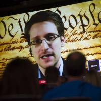Fugitive former U.S. National Security Agency contractor Edward Snowden speaks on a screen during a virtual conversation at the South By Southwest Interactive Festival in Austin, Texas, in March. | BLOOMERG