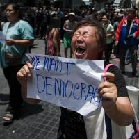 An anti-coup protester screams at soldiers during a planned gathering in Bangkok on Sunday. The leader of Thailand's military junta said Monday that the country's king had officially endorsed him to run the nation after the armed forces seized power last week. | AFP-JIJI