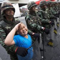 A boy poses with Thai soldiers near Bangkok's Victory Monument on Friday. | AP