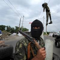 A masked pro-Russian gunman wearing a ribbon of St. George guards a checkpoint near the eastern Ukrainian city of Slovyansk on Friday. | AFP-JIJI