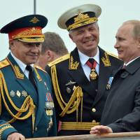 Russian President Vladimir Putin speaks with Defense Minister Sergei Shoigu (left) during his visit to the Crimean port of Sevastopol on Friday. | AFP-JIJI