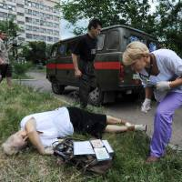 An elderly woman was among at least two civilians reported dead Monday after fighting between government troops and pro-Russian separatists in the city of Slovyansk. A medical crew is seen attending the woman's body. | AFP-JIJI