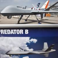 A Predator drone manufactured by General Atomics Aeronautical Systems Inc. is display outside the company's stand on the second day of the Paris Air Show in June 2013. The U.S. signaled Tuesday that it will publicly reveal a secret memo describing its legal justification for using drones to kill U.S. citizens suspected of terrorism overseas. | BLOOMBERG