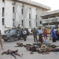 People gather around the bodies of killed Somali soldiers after an attack on parliament in Mogadishu on Saturday.   AFP-JIJI