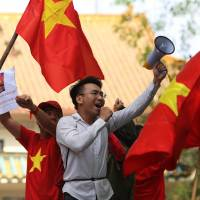 Anti-China protesters wave Vietnamese flags and shout slogans in front of the Chinese Embassy during a rally in Hanoi on Sunday. | AFP-JIJI