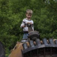 A boy stands atop a seized armored personnel carrier that was set alight during a fighting between pro-Russian militants and government troops in the village of Oktyabrskoye in eastern Ukraine on Wednesday. | AP