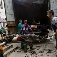 Medical workers and pro-Russian activists unload the bodies of pro-Russian fighters from a truck in the eastern Ukrainian city of Donetsk on Tuesday. Fierce clashes between Ukrainian government forces and rebels left scores of insurgents dead.   AFP-JIJI