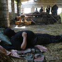 A member of the pro-Ukrainian 'Donbass Battalion' rests inside a base in the town of Velyka Novosilka, in eastern Ukraine's Donetsk region, on May 17. | REUTERS