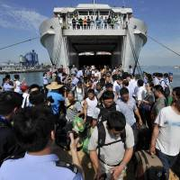 Chinese citizens evacuated from Vietnam arrive at Xiuying port in Haikou, southern China's Hainan province, on Tuesday. More than 3,500 Chinese citizens have been evacuated from riot-hit Vietnam by sea as Hanoi stifled fresh protests over a territorial dispute and foreign investors counted the cost. | AFP-JIJI