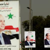 Campaign posters urge support for presidential candidate and former army chief Abdel-Fattah el-Sissi in Cairo on Sunday, a day ahead of presidential elections in Egypt. | AFP-JIJI