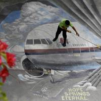 A school utility worker mops a mural depicting the missing Malaysia Airlines Flight 370 on April 8 at the Benigno 'Ninoy' Aquino High School campus in Makati city, east of Manila. | AP