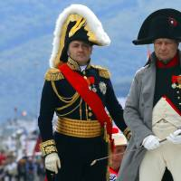 A man playing French Emperor Napoleon Bonaparte (right) and other people dressed in 19th-century French uniforms Sunday re-enact the exiled leader's 1814 landing in Portoferraio on the Italian island of Elba. | AP