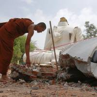 A monk checks a Buddha statue that was damaged by an earthquake at the Udomwaree temple in Chiang Rai, in northern Thailand, on Tuesday. | REUTERS