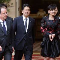 French President Francois Hollande, Prime Minister Shinzo Abe and his wife, Akie, arrive for a state dinner at the Elysee Palace in Paris on Monday. | AFP-JIJI
