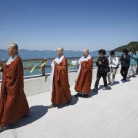 Buddhist monks, believers and family members of the missing passengers on the sunken passenger ferry Sewol march during a service in memory of the missing and dead passengers at a port in Jindo on Tuesday, Buddha's birthday. | REUTERS