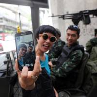 A woman takes a selfie with Thai soldiers stationed at the Ratchaprasong intersection in central Bangkok on Tuesday. Two days later, the army imposed martial law nationwide after months of political turmoil that brought down an elected leader and tipped the economy into a contraction. | BLOOMBERG