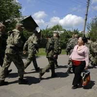 A local woman welcomes armed pro-Russia militiamen marching toward a polling station during a referendum on self-rule in the eastern Ukrainian city of Slovyansk on Sunday. | REUTERS