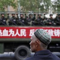 A Uighur man looks at a truck carrying paramilitary policemen during an anti-terrorism rally in Urumqi, the capital of China's Xinjiang region, on Friday. | REUTERS
