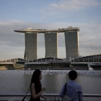 People stroll along the waterfront near the Marina Bay Sands hotel and casino in Singapore last December. Prime Minister Shinzo Abe plans to visit a casino and resort complex in the city-state later this month to gauge the economic effects of legalizing casinos in Japan. | BLOOMBERG