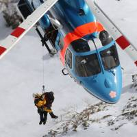 A Nagano Prefectural Police rescue squad on a helicopter lift an unidentified climber from Mount Hotaka on Tuesday. | KYODO